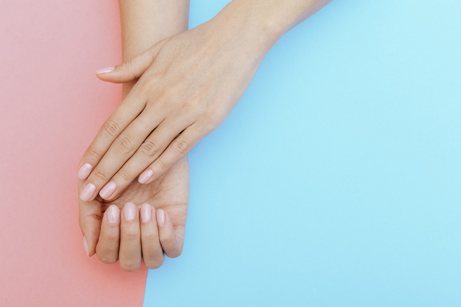 Manicured nails with light pink acrylic nail polish