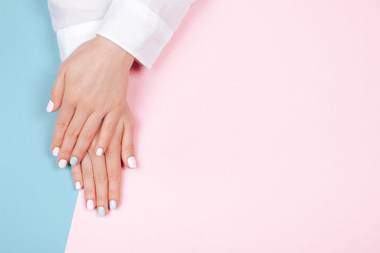 folded hands with pink and blue acrylic dip powder manicure