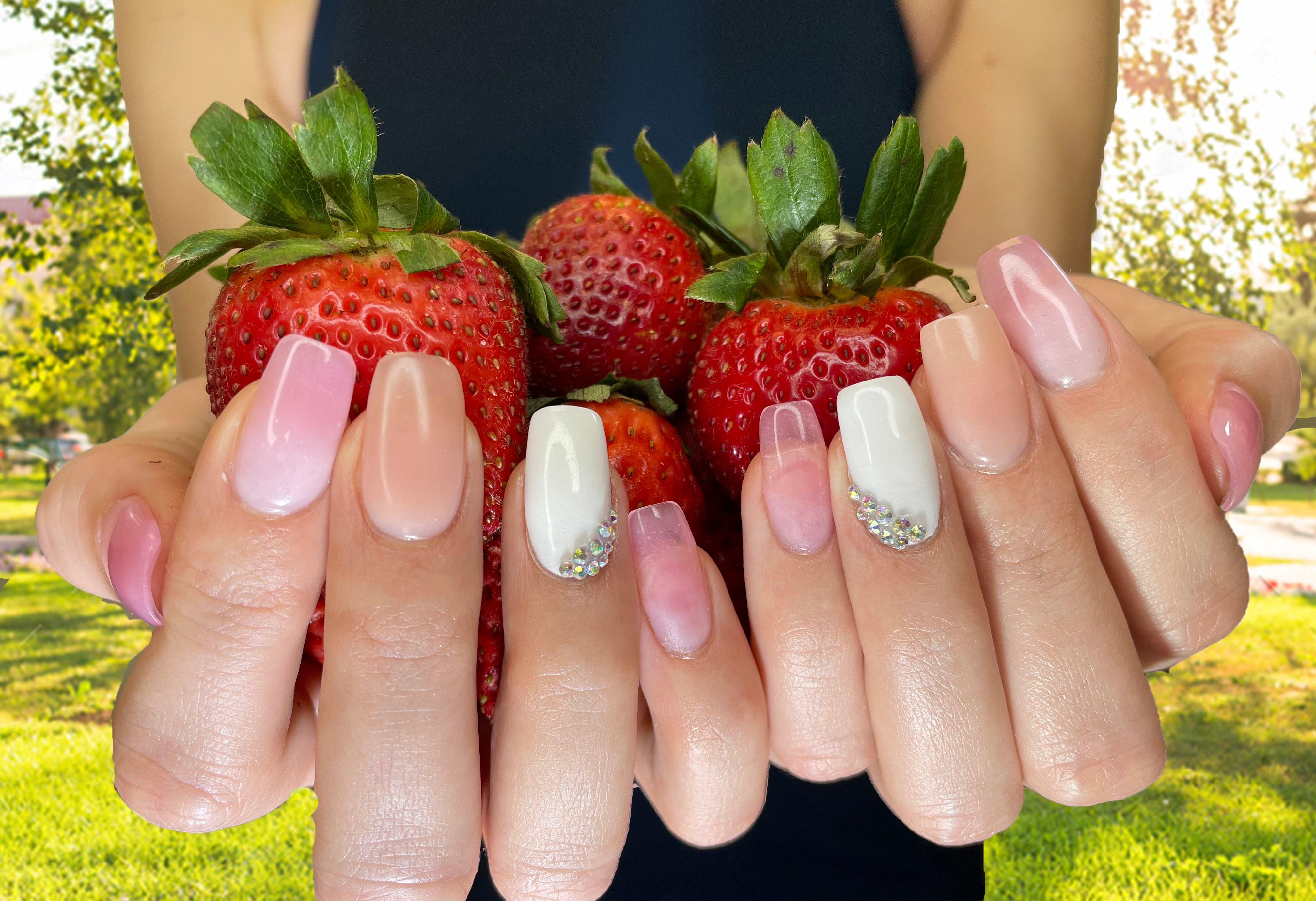 pink and white acrylic nails holding strawberries